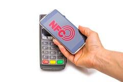 Betalning i handel med nfcsystemet med en mobiltelefon Bästa sikt, vit bakgrund Arkivbild