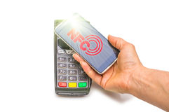Betalning i handel med nfcsystemet med en mobiltelefon Bästa sikt, vit bakgrund Royaltyfri Fotografi