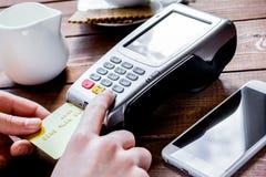 Betalning i kafébegrepp med kortet och terminal på träbackgro Royaltyfri Foto