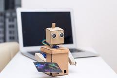 Betalning vid kortet på linje Robot som rymmer en kreditkort Arkivfoto