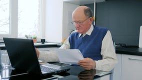 Betalningarbetar online-morfadern på bärbara datorn i internet med dokument in i armar som sitter på tabellen arkivfilmer