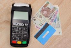 Betalningterminal med kreditkort- och polermedelpengar på skrivbordet, finansbegrepp Royaltyfri Foto