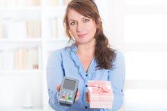 Betalningterminal och gods för säljare hållande Arkivfoto