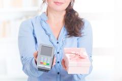 Betalningterminal och gods för säljare hållande Arkivfoton