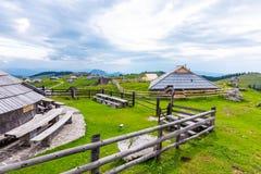 Betar den stora platån för den Slovenien velikaplaninaen, jordbruk land nära staden Kamnik i slovenska fjällängar Trähus på grönt arkivfoton