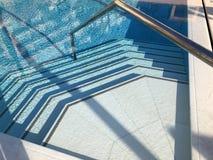 Betegelde stappen van een fonkelend zwembad stock foto
