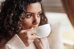 Beteiligte Afroamerikanerfrau, welche die Tasse Tee trinkt Lizenzfreie Stockbilder