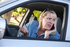 Beteiligte Frau, die Handy beim Antreiben verwendet Lizenzfreie Stockfotos