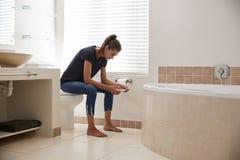 Beteiligte Frau im Badezimmer unter Verwendung des Hauptschwangerschaftstests lizenzfreies stockfoto