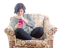 Beteiligte Frau im Sofa, das Telefon betrachtet Stockfotografie