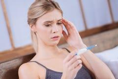 Beteiligte junge Frau, die Thermometer betrachtet Lizenzfreie Stockbilder