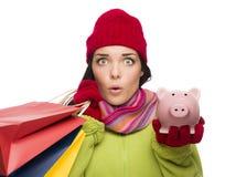 Beteiligte Mischrasse-Frau, die Einkaufstaschen und Piggybank hält Stockbild