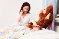 Beteiligte Mutter, die am Telefon spricht Stockfotos