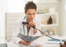 Beteiligter Doktor mit dem fluorography, das Telefon hält Stockbild