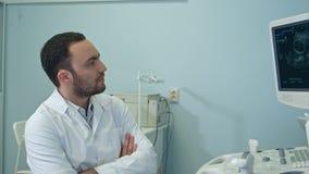 Beteiligter männlicher Doktor, der Ultraschallscan analysiert Stockbilder