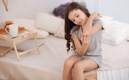 Beteiligtes kleines Kind, das zu Hause ihre Wunde behandelt Lizenzfreie Stockbilder