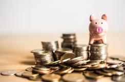 Betekenis van het concept van het besparingsgeld met spaarvarken over de muntstukken stock fotografie