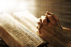 Beten über einer Bibel Stockfotografie