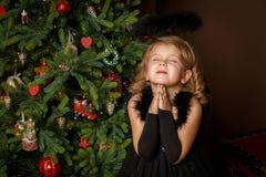 Beten Sie ein kleines Mädchen in einem schwarzen Engelskostüm und mit Hoffnung nach Frieden suchen Glückliche Kindheit und Friede Stockbild