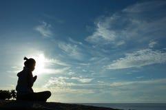 Beten am Sonnenaufgang auf Insel Stockfoto