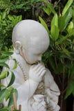 Betende Buddha-Jungen-Statue im Garten Stockfotografie