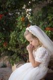 Betende erste heilige Kommunion des Mädchens Lizenzfreie Stockbilder