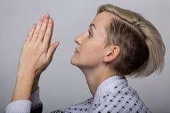 Betende erwachsene blonde Frau Stockbild