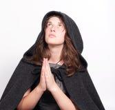 Betende Frau in der schwarzen Haube auf Weiß Stockfotos