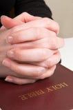 Betende Hände auf Bibel Stockfoto