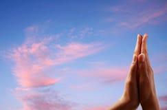 Betende Hände auf Himmelhintergrund Stockfoto