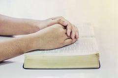 Betende Hand von Männern auf offener Bibel buchen Lizenzfreie Stockbilder