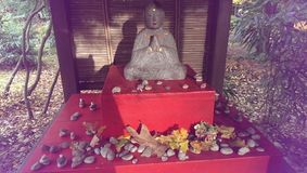 Betende Mönchstatue mit Herbstlaub lizenzfreie stockbilder