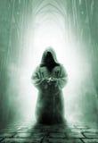 Betender mittelalterlicher Mönch im dunklen Tempelkorridor Lizenzfreies Stockfoto