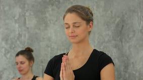 Betendes oder übendes Yoga der schönen blonden Frau zu Hause, Händchenhalten im namaste Lizenzfreie Stockfotos