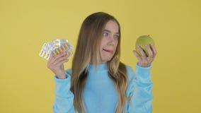 Beter таблеток! Женщина держа Витамин C пакета волдыря таблеток в одной руке и яблоко в других Выбор между естественным и сток-видео