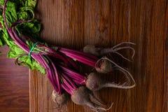 A beterraba vermelha com verde da pastagem sae no fundo rústico Beterrabas orgânicas detox Foco seletivo imagens de stock royalty free