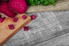 Beterrabas inteiras e cortadas e salsa fresca em um pano claro e em um fundo de madeira Vegetais de um jardim imagem de stock