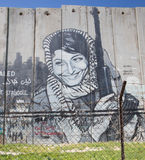 BETHLEHEM, ISRAEL - MARCH 6, 2015: The Detail of graffitti on the Separation barrier. Palestinian woman with the weapon Royalty Free Stock Images