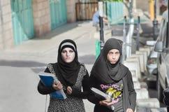 Bethlehem, Palestina Estudantes fêmeas que andam abaixo da rua no vestido nacional Foto de Stock