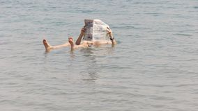 BETHLEHEM, PALESTINE- SEPTEMBER, 22, 2016: a man floats in the dead sea of israel and reads a newspaper stock video footage