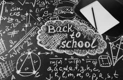 Betitla tillbaka till skolan, formler som är skriftliga vid vit krita på den svarta svart tavlan för skolan, och anteckningsboken Royaltyfria Foton