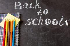 Betitla tillbaka till skolan som är skriftlig vid vit krita och anteckningsboken med färgrika blyertspennor på den svarta svart t Royaltyfri Bild