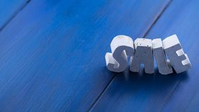 Beton letters on a wooden board. The sale word from the beton letters on the blue wood Royalty Free Stock Photo