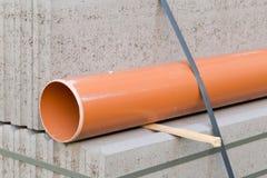Betonblöcke und Plastikpvc-Abwasserleitung auf Palette auf constr Lizenzfreies Stockbild
