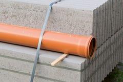Betonblöcke und Plastikpvc-Abwasserleitung auf Palette auf constr Stockbild