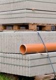 Betonblöcke und Plastikpvc-Abwasserleitung auf Palette auf constr Stockfotos