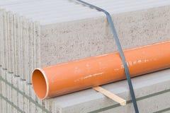 Betonblöcke und Plastikpvc-Abwasserleitung auf Palette auf constr Lizenzfreie Stockfotos