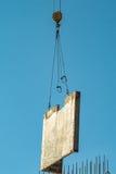 Betonblock wird durch einen Kran gehalten Lizenzfreie Stockbilder