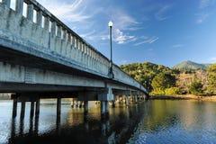 Betonbrücke mit hellem Pfosten über Fluss stockfotos