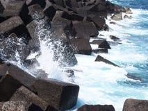 Betongkubvågbrytare med blått som kraschar vågor och bränning i t Arkivbilder